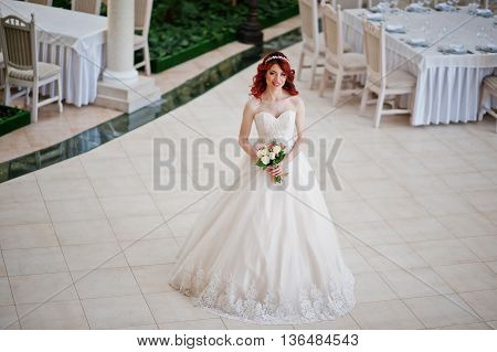 Charming Red-haired Bride With Wedding Bouquet At Hand Posed Against The  Great Wedding Hall With Ta