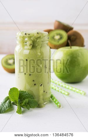 Fresh homemade kiwi juice in a glass jar on white background.