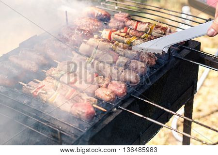 Farmer man cooking meat on barbecue - Chef putting some meat skewers on grill in park outdoor - Concept of eating outdoor during summer time - Soft focus on barbecue tongs - Soft saturated warm filter