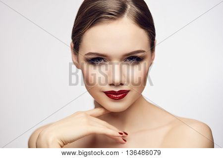 Gorgeous young blond woman with red lips flirting with camera. Shallow depth of field