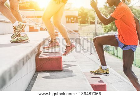 Athletic people running in stadium on terrace stairs - Multiracial runners training at sunset outdoor - Healthy lifestyle and sport concepts - Soft focus on center shoes