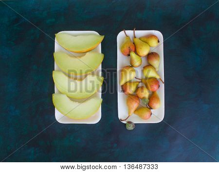 Pear and melon on a dark background