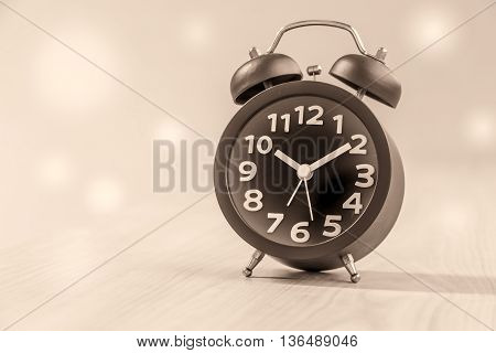 Soft and blurred black clock on wood table made vintage style background
