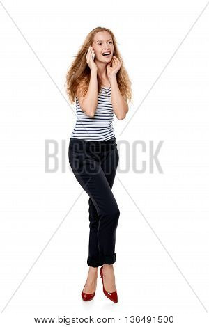 Full length portrait of young, happy laughing beautiful woman talking on cell phone looking to the side at blank copy space, over white background