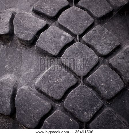 Close-up of tractor tire tread as background.