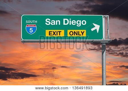 San Diego exit only 5 freeway sign with sunrise sky.