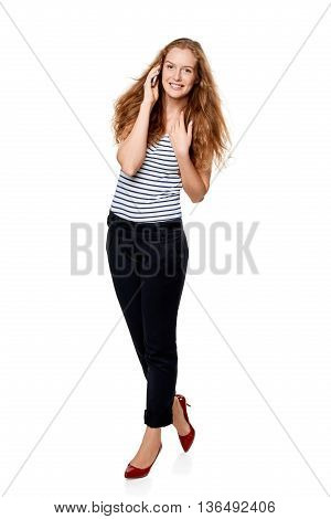 Full length portrait of young, happy beautiful woman talking on cell phone looking at the camera, over white background