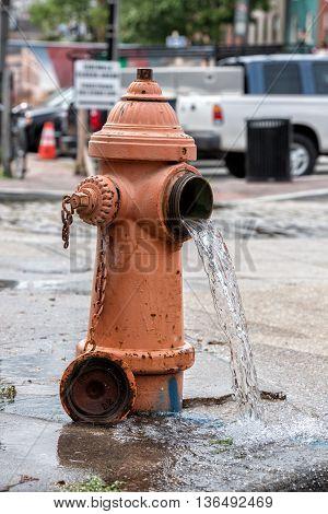Street Orange Hydrant Spreading Water On The Street