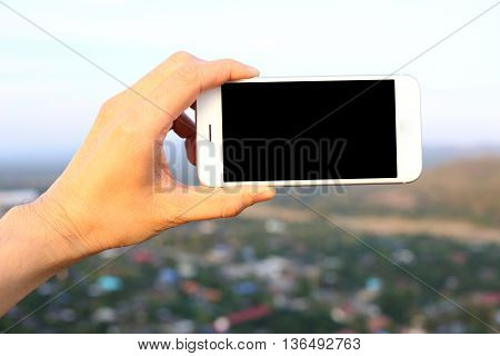 Hand holding white smartphone with city background