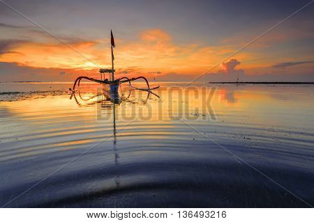 Traditional Balinese ships Jukung in Sanur beach at sunrise Bali Indonesia
