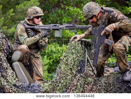BURG / GERMANY - JUNE 25 2016: german soldier fires with machine gun on open day in barrack burg / germany at june 25 2016