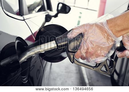 closeup of a young caucasian man filling the fuel tank of a car