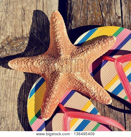 closeup of a pair of colorful flip-flops and a starfish on a weathered wooden pier