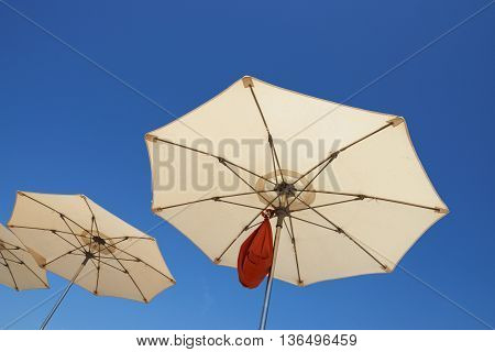 Beach Parasols Are On Bright Blue Sky Background.