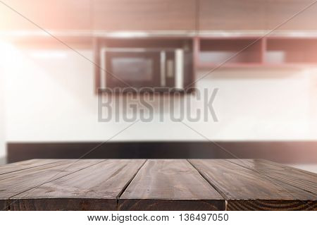 Empty wooden table over blurred kitchen background.