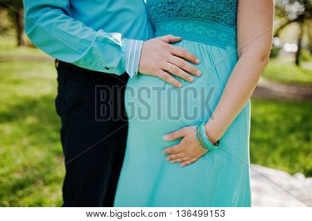 Pregnant Woman And Her Husband Holding Hands On Tummy. New Life Theme