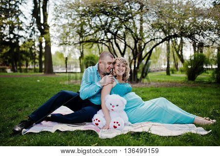 Happy Pregnant Couple Hugging And Sitting On Plaid Background Spring Nature