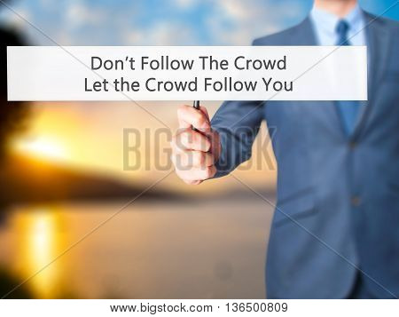 Don't Follow The Crowd Let The Crowd Follow You - Businessman Hand Holding Sign