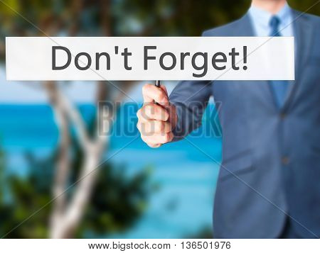 Don't Forget! - Businessman Hand Holding Sign