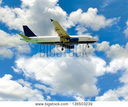 The airplane in the blue sky with clouds