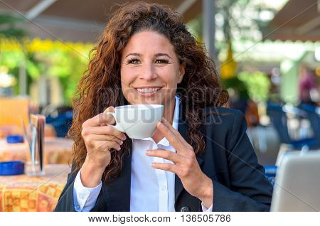 Exultant young woman enjoying a cup of coffee as she sits at an open-air cafe looking over the cup with a wide beaming joyful smile