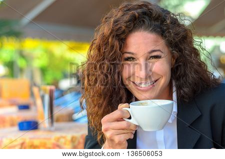 Exultant young woman enjoying a cup of coffee as she sits at an open-air cafe looking over the cup at the camera with a wide beaming joyful smile