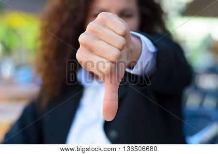 Woman making a thumbs down gesture to show disapproval failure or negativity focus to her hand