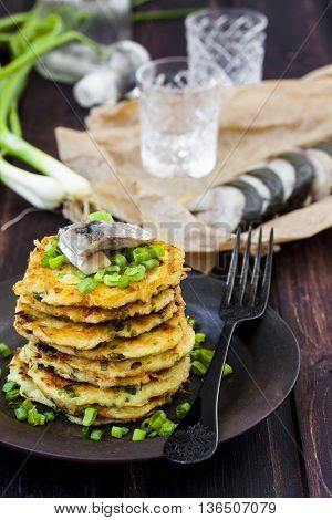 potato pancakes with herring and onion on a dark background