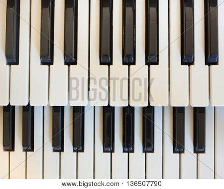 Top down view of piano keys in natural light .