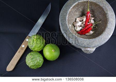 Chili, garlic in stone mortar and lemon,kaffir,kinfe Thai food ingredients
