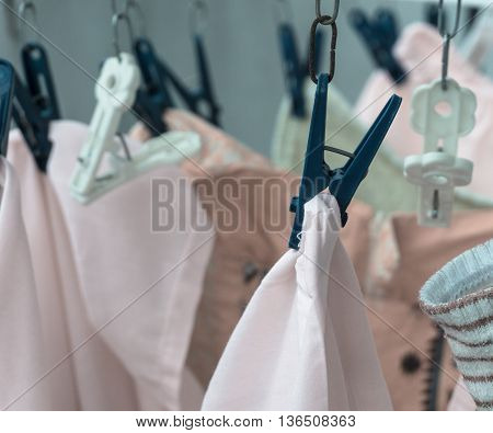 Low key colorful clothes dry hanging with blue clothes peg on clothesline symbolic of rainy day with colored filter effect and selective focus