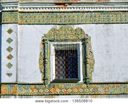 Window framed with colorful ancient mosaic tiles. Nicholas Vyazhischsky stauropegic monasteryVeliky Novgorod Russia. Ornamental architecture architecture view closeup of architecture details