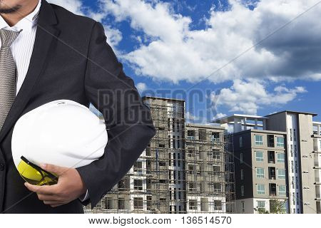 Engineer Holding White Helmet For Workers Security On Background Of New Highrise Apartment Buildings