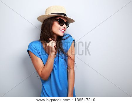 Happy Enjoyment Young Woman In Sun Glasses And Hat Posing On Blue Background