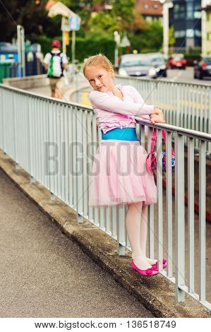 Outdoor portrait of a cute little girl of 7 years old, walking to dance school and dancing in the street, wearing dance skirt tutu