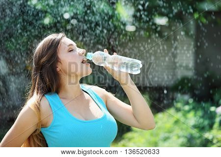 Beautiful young woman drinks water from a bottle
