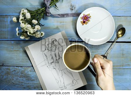 Top view of woman hand painting a sketch on wooden table with white flower and cup of coffee