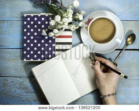 Top view of woman hand writing in notebook on wooden table with white flower and cup of coffee