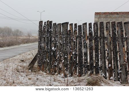 Wooden fence in the snow near the building under construction