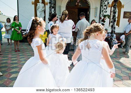 Mukyluntsi , Ukraine - 26 June, 2016: First Holy Communion. Children Stay Near Christian Church. Bab