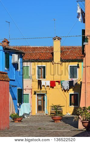 Courtyard with dried linens between colorful houses on the famous island Burano Venice . Venice and the Venetian lagoon are on the UNESCO World Heritage List. Warm evening light
