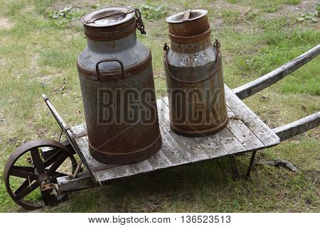 Two old milk buckets on a old wheelbarrow picture from the North of Sweden.