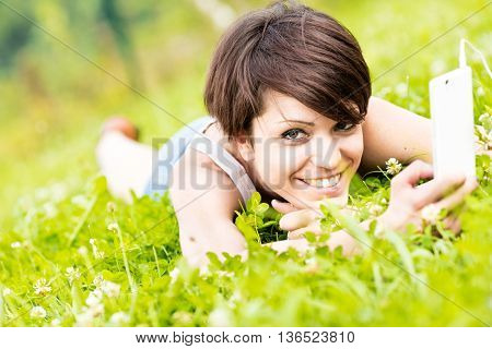 Young Woman Lying In Grass Listening To Music