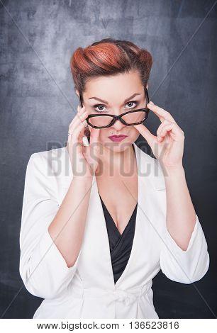 Serious Teacher In Glasses On Blackboard Background