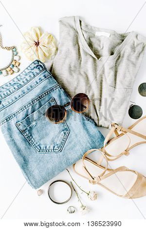 flat lay feminini clothes and accessories collage with shirt jeans shorts sunglasses bracelet sandals earrings on white background.