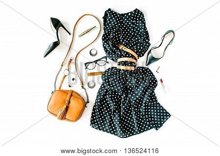 flat lay feminini clothes and accessories collage with black dress glasses high heel shoes purse watch mascara lipstick earrings on white background.