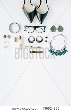 flat lay feminini accessories collage with glasses high heel shoes mascara lipstick bracelet earrings necklace and bow tie clips on white background.