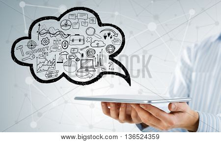 Hand of businessman showing tablet with business sketches in cloud