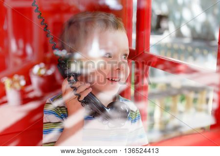 happy boy smiling while talking on the phone. shot through the glass of red telephone box. blur, reflections, blurred motion due to the concept. sharing emotions, impressions and feelings.