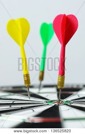Selective focus of darts hitting on dartboard with white background